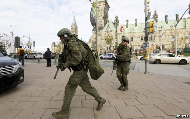 Armed RCMP officers head towards the Langevin Block on Parliament Hilll