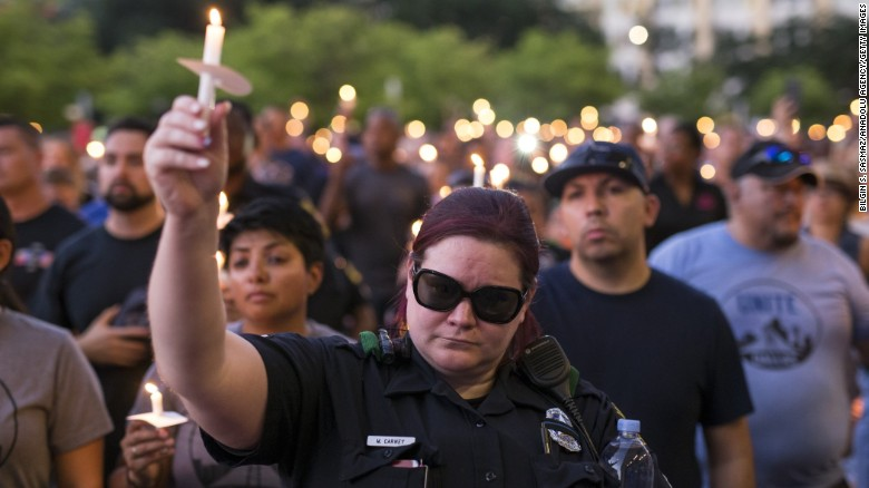 Mourners attend a Monday candlelight vigil for five officers killed last week during protests in Dallas.