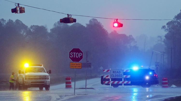 Authorities in Brooks County, Ga., block Highway 122 as power line workers repair a downed pole on Jan. 22, 2017, near Barney, Ga.