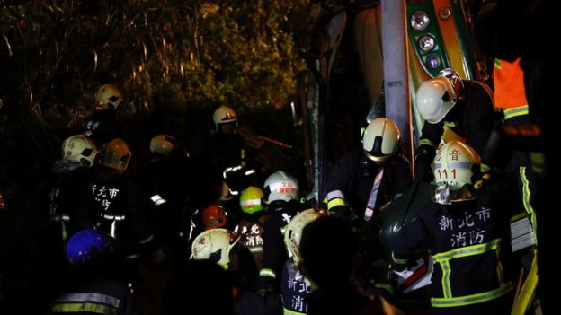 Rescuers look for survivors in a crashed bus after an accident on a highway in Taipei, Taiwan February 13, 2017