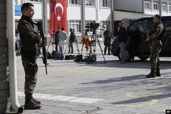 Turkish police officers stand guard outside a polling station in Ankara, April 16, 2017.
