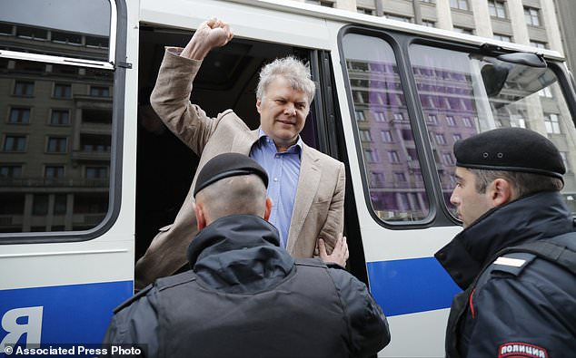 Russian police detain Yabloko Party leader Sergei Mitrokhin as protesters gather to rally against Moscow City's project to pull down Soviet-era apartment blocks outside the Kremlin in front of the state Parliament building in Moscow, Russia, Wednesday, June 14, 2017. Several people have been detained outside the Russian parliament at an impromptu protest against a controversial plan to tear down Soviet-era apartment blocks and relocate 1.6 million people. (AP Photo/Alexander Zemlianichenko)
