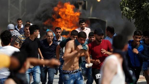 Palestinian youths run from the path of an Israeli army bulldozer during clashes in the village of Kubar, west of Ramallah, on July 22, 2017, as Israeli forces try to close the roads leading to the village. Stabbings and clashes that left six people dead raised fears of further Israeli-Palestinian violence as tensions mount over new security measures at a highly sensitive Jerusalem holy site. (ABBAS MOMANI/AFP PHOTO)