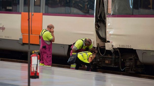 Railway technicians check a train carriage at Francia station in central Barcelona on 28 July 2017 after a regional train hit the buffers inside the station